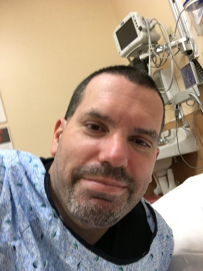 Somehow sort-of smiling despite being in serious pain in the hospital just before 5 a.m.